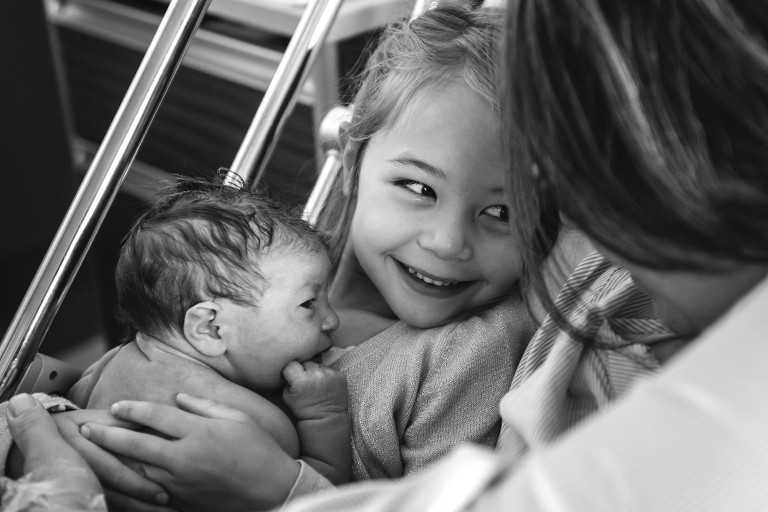girl holding her newborn brother at the hospital in Montreal